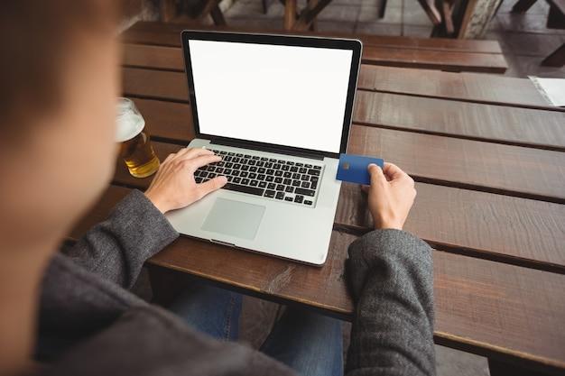 ノートパソコンにクレジットカードでオンラインショッピングをしている男