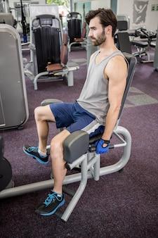 ジムで脚のウェイトマシンを使用して焦点を当てた男