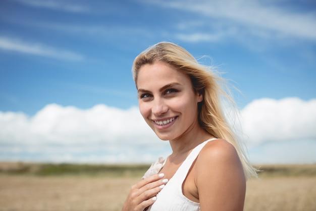 Портрет беззаботной женщины, стоя в поле