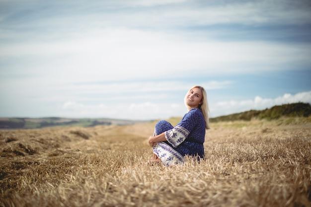 Белокурая сидя женщина поля
