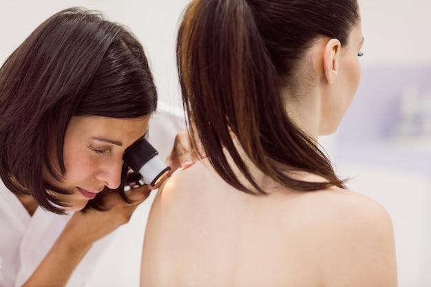 皮膚科医が患者の皮膚をダーマスコープで検査