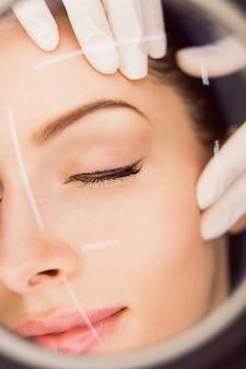 皮膚科医が女性患者の皮膚を調べる