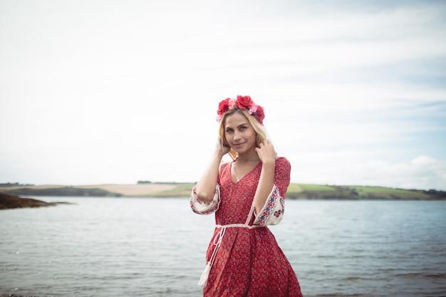 川の近くに立って花ティアラを着ている金髪の女性