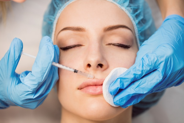 Пациентка, получающая укол на лице