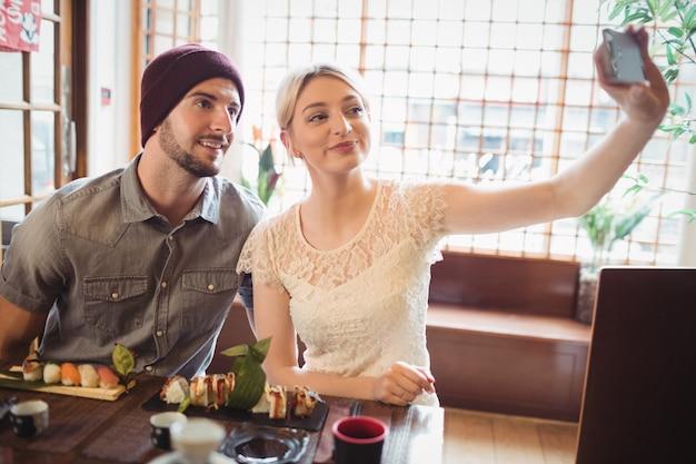 Пара, делающая селфи, имея суши