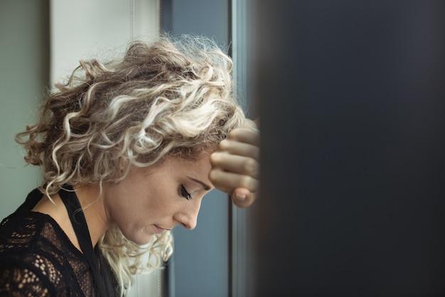 Расстроенная деловая женщина, опираясь на окно