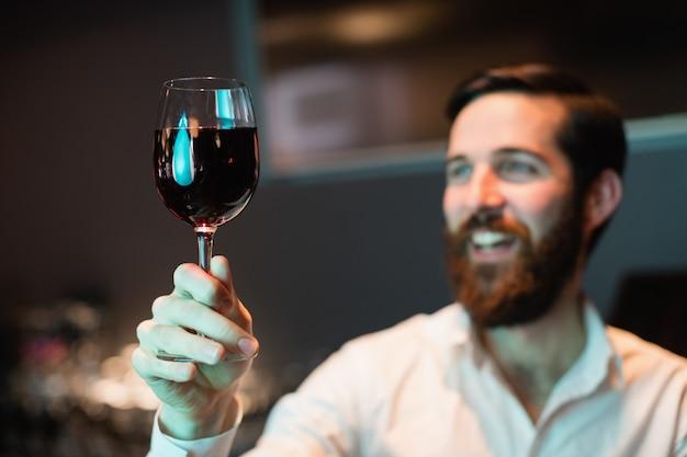 Бармен смотрит на бокал красного вина