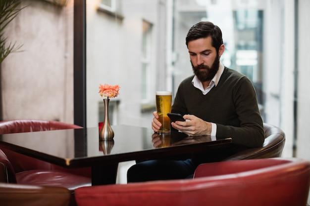 Человек с помощью мобильного телефона, имея бокал пива