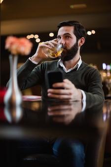 Мужчина держит мобильный телефон и выпить