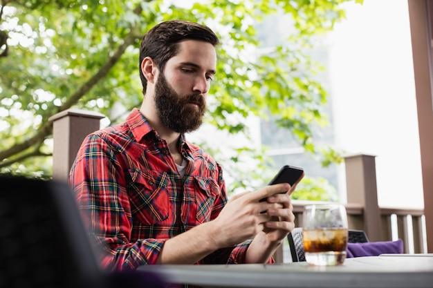 Человек с помощью мобильного телефона в баре
