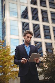 Бизнесмен держа мобильный телефон и используя цифровую таблетку