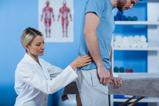Физиотерапевт осматривает человека обратно
