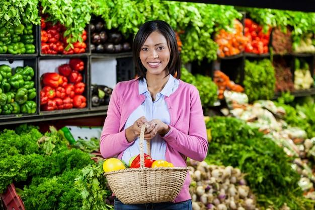 バスケットに果物と野菜を持って笑顔の女性
