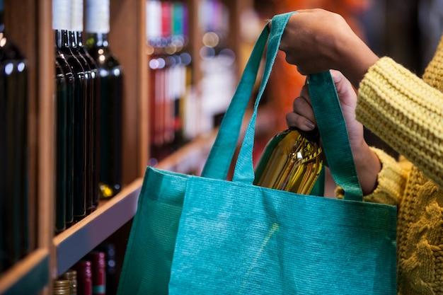 Женщина кладет бутылку вина в сумку
