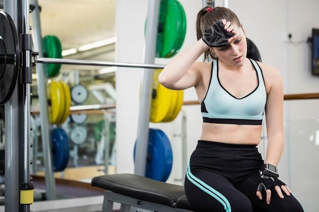 Утомленная женщина сидя на скамье штанги в спортзале