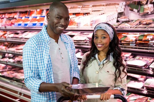 スーパーマーケットの食料品のセクションで買い物笑顔のカップル