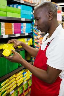 Мужской персонал расставляет товары на полке в продуктовом отделе