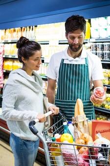 Улыбающийся мужской персонал помогает женщине с покупками продуктов