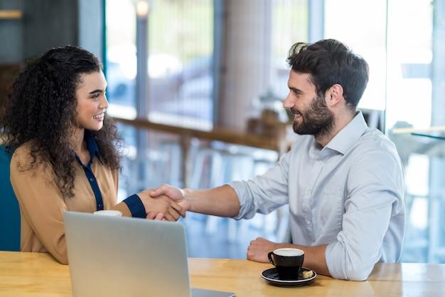 Пара пожимает руку в кафе