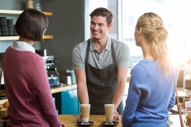 Официант подает чашку кофе клиенту на стойке
