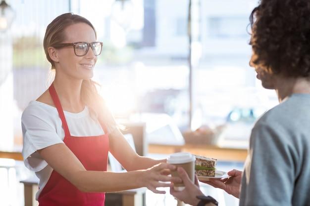 Официантка подает кофе и бутерброд клиенту в кафе