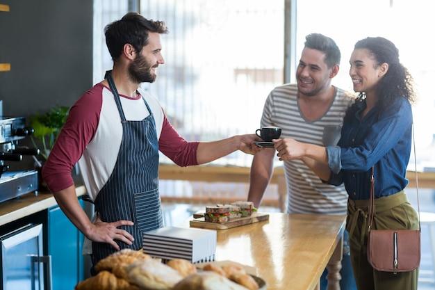 Официант, подающий кофе клиенту на стойке
