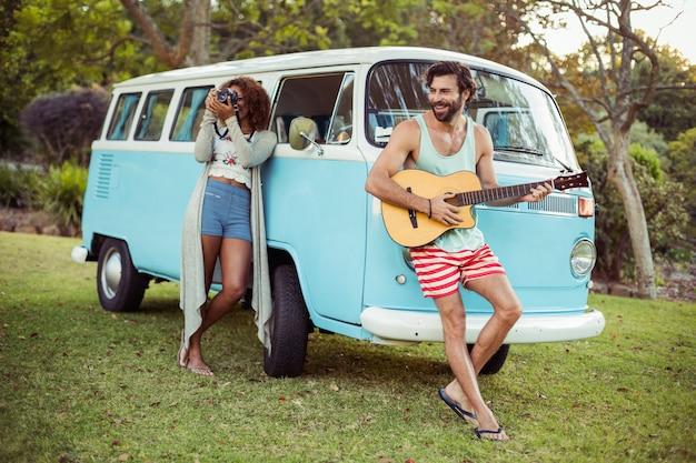 キャンピングカーの近くでギターを弾く男と彼のそばに撮影する女性