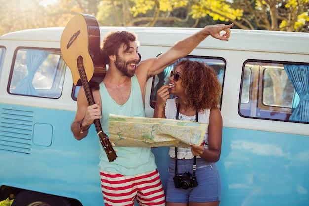 キャンピングカー近くの地図を探しているカップル