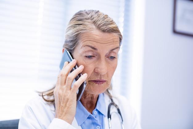 Женский доктор разговаривает по мобильному телефону