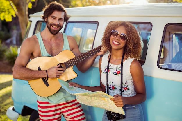 キャンピングカーの近くでギターを弾く男と彼のそばに地図を持っている女性
