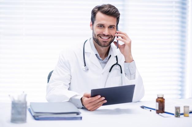 Мужской доктор разговаривает по мобильному телефону при использовании цифрового планшета