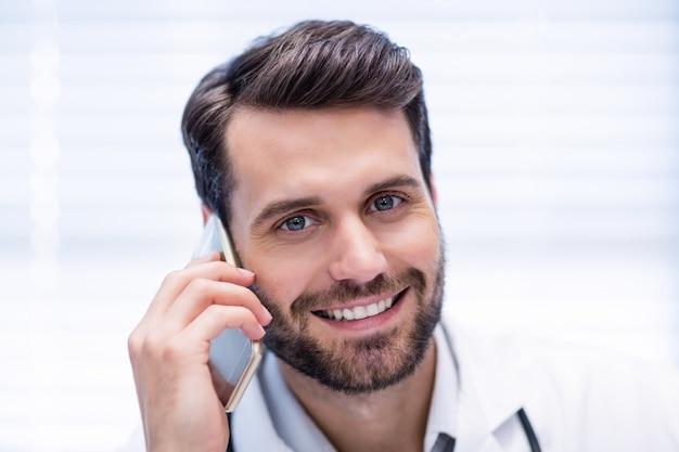 Портрет мужчины доктор разговаривает по мобильному телефону