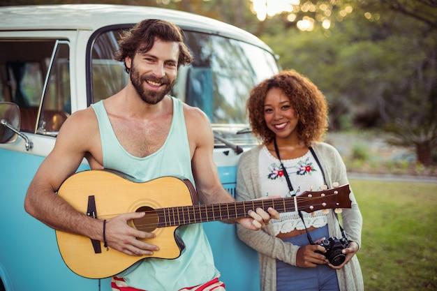 彼のそばに立っている女性ながらキャンピングカーの近くでギターを弾く男