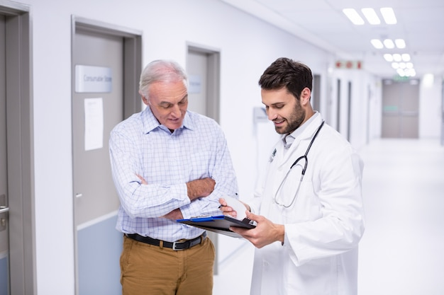 医師と患者の廊下でクリップボードで議論