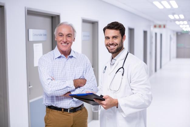 医師と患者の廊下でクリップボードで議論の肖像画