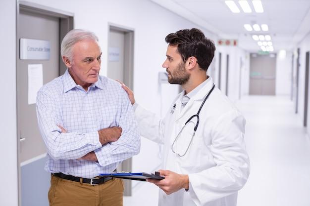 廊下で患者と相互作用する医師