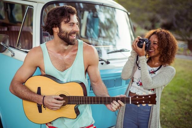 女性がカメラで撮影しながらギターを弾く男