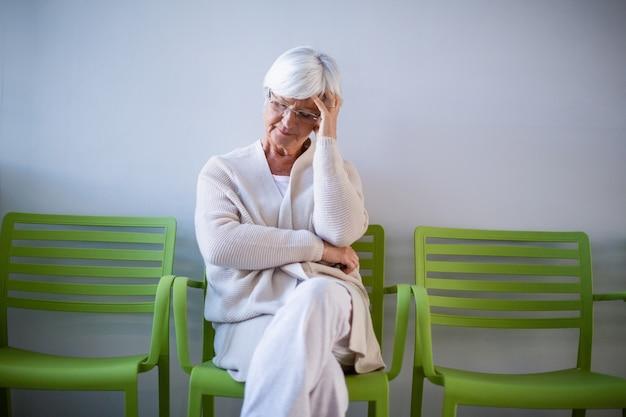 待合室の椅子に座って緊張した年配の女性