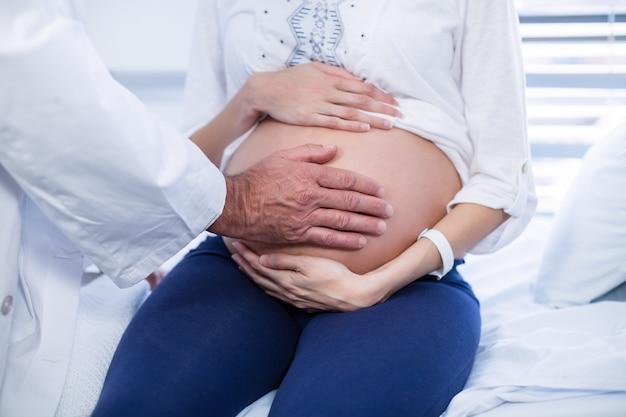病棟の妊婦の腹に触れる医師の中央部
