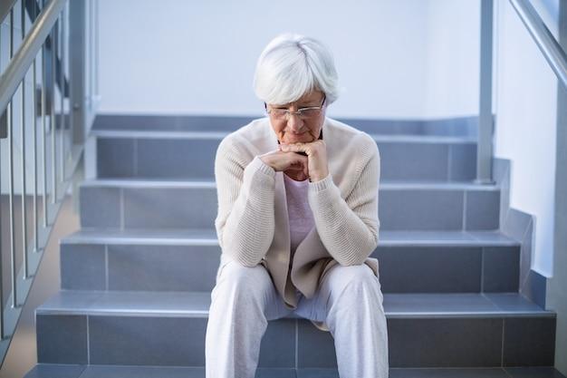 Расстроенная старшая женщина сидя на лестницах