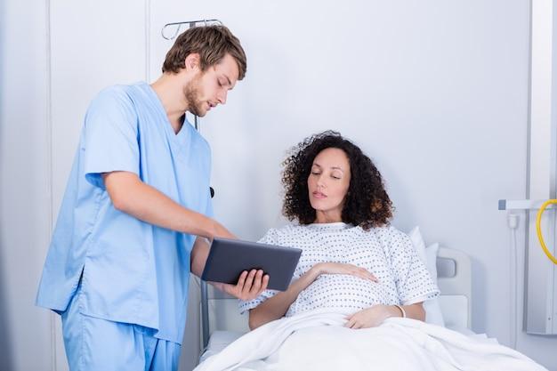 病棟のデジタルタブレットで妊娠中の女性を支援する医師