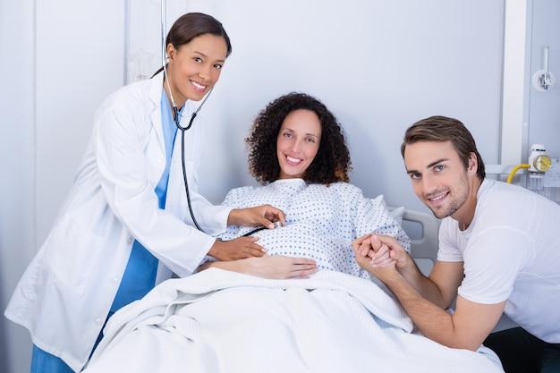 区で妊娠中の女性を調べる医師の肖像画