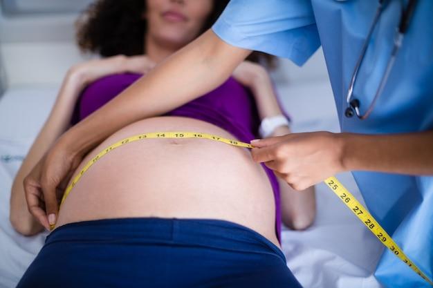 Доктор измеряет живот беременной женщины в палате