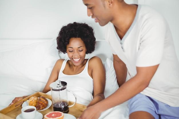 Красивый мужчина приносит завтрак своей девушке на кровати