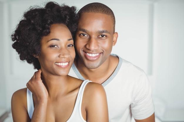 カメラを見て寝室で笑顔のカップルの肖像画