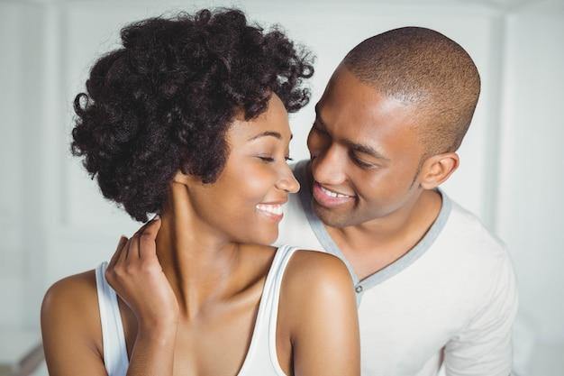 自宅でお互いを見て笑顔のカップル