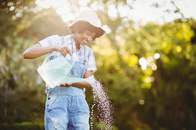 笑顔の女性が庭の植物に水をまく