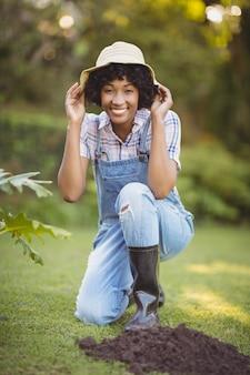 彼女の帽子を保持している庭で身をかがめる笑顔の女性