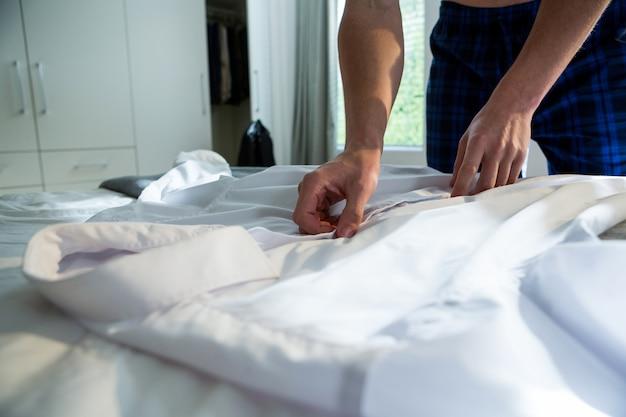 男の寝室で彼の白いシャツのボタンを外す