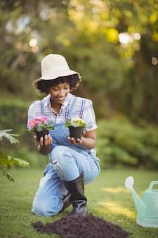 花を持って庭で身をかがめる笑顔の女性